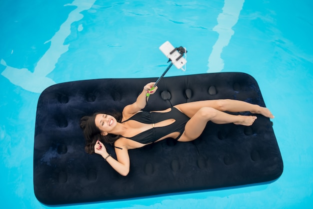 Girl lying on an inflatable mattress in swimming pool and makes selfie photo on the phone with selfie stick