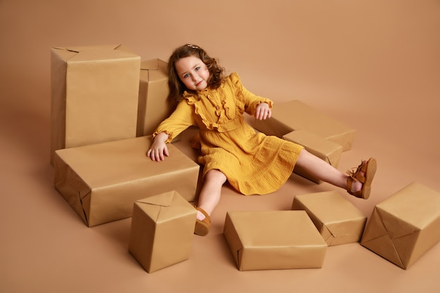 Girl lying in the middle of scattered boxes with gifts as doll