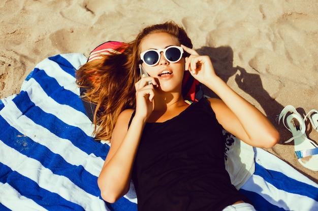 少女は、携帯電話で話してビーチでのタオルの上に横たわります