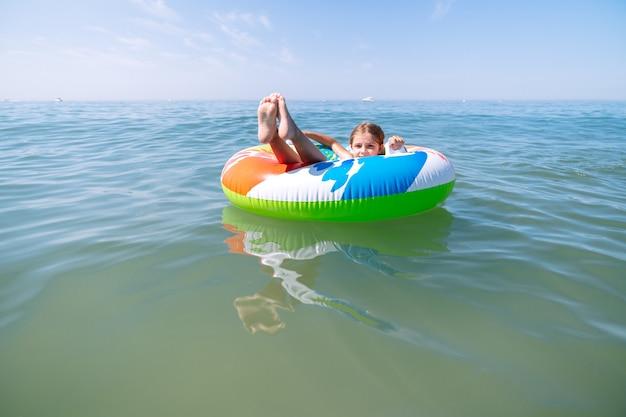 여름 방학에 푸른 바다 한가운데서 자신을 즐기는 다채로운 풍선 매트리스에 누워있는 소녀