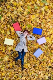 カラフルな買い物袋の近くに紅葉の上に横たわっている女の子