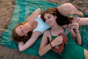 Girl lying on beach laughing at her friend playing ukulele