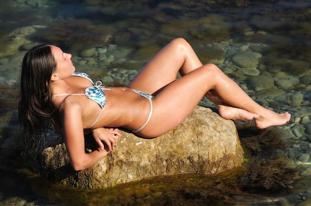 海岸の岩の上に横たわっている女の子
