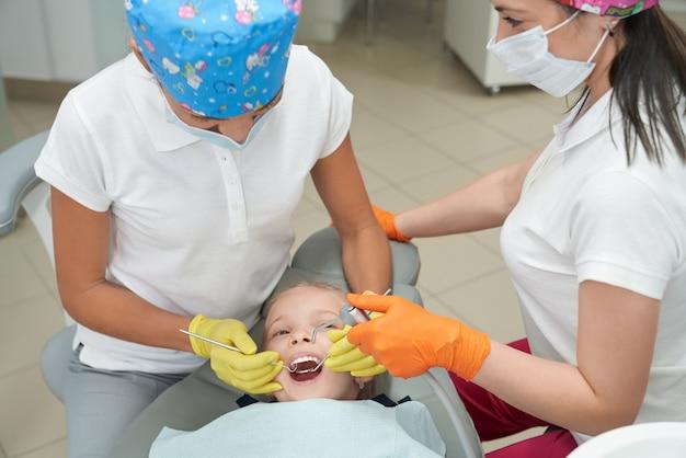 口を開けて椅子に横になっていると歯科医を見て女の子