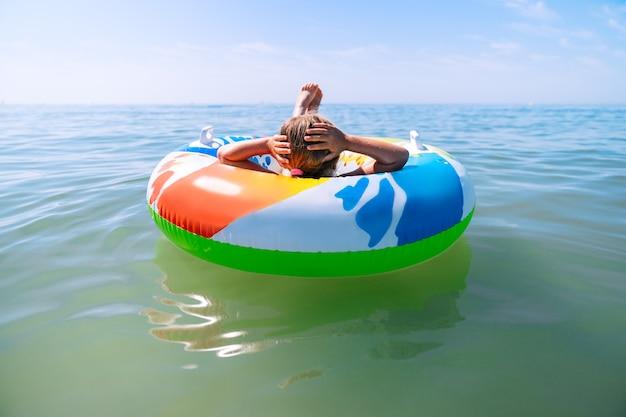 여름 휴가에 푸른 바다 한가운데에서 휴식을 즐기는 다채로운 풍선 매트리스 휠 플로트에 그녀를 다시 누워 소녀