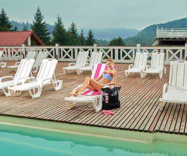 プールの近くのラウンジャーで横になっていると、日中の日焼けの女の子。