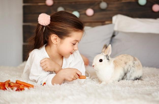 침대에 누워 토끼에게 먹이를 주는 소녀