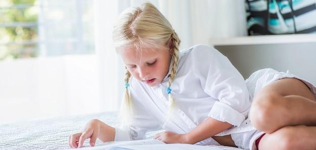 Девушка лежит на кровати и читает книгу