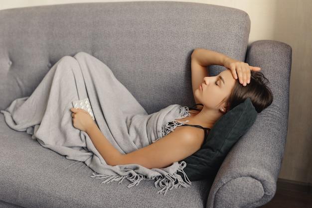 ソファーで横になり、頭を抱え、インフルエンザを感じている少女。家に。
