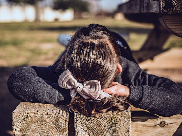 Girl lying outdoors on a wooden bench