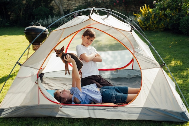 Girl lying and playing with dog in front of her little brother in tent