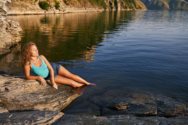 Girl lying on rocky shore lowering her feet into water.