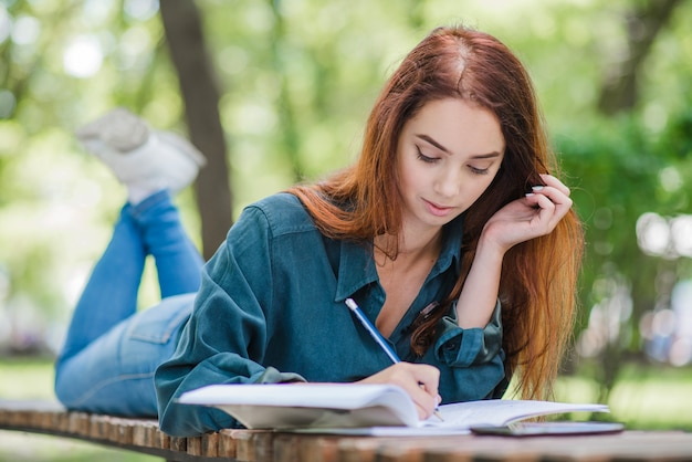 Girl lying on table in park writing