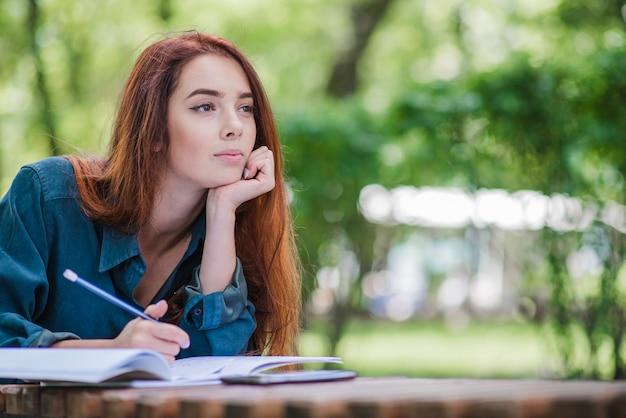 Ragazza sdraiata sul tavolo nella scrittura del parco
