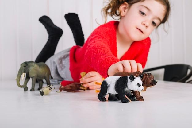 Girl lying on table playing with animal toys