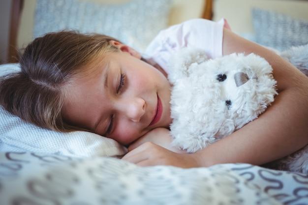 テディベアと横たわっている少女