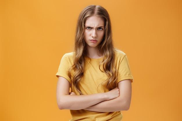 悪魔のように怒っている女の子。額の下から眉をひそめ、防御的なポーズで胸に交差する腕をやめ、犯罪者を軽蔑している怒っている気になって気分を害した憎むべき若い女性の肖像画。