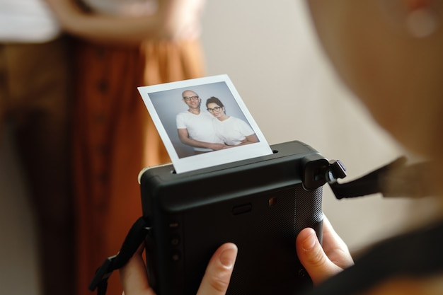 Girl made a photo of her parents with a instant camera at home