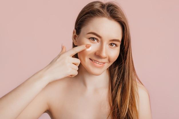 Девушка делает маски красоты лица. крем против морщин для свежести кожи вокруг глаз. женщина позаботится о молодой коже. модель смеется и развлекается в спа на розовом фоне