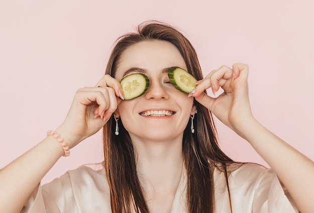 Девушка делает самодельные маски красоты для лица. огурцы для свежести кожи вокруг глаз. женщина позаботится о молодой коже. модель смеется и развлекается в спа на розовом фоне