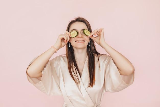 女の子は自家製の顔の美容マスクを作ります。目の周りの肌の鮮度を保つきゅうり