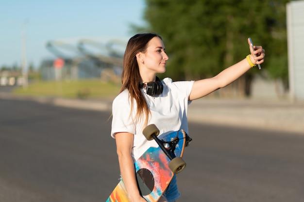 Girl make selfie with longboard on mobile phone