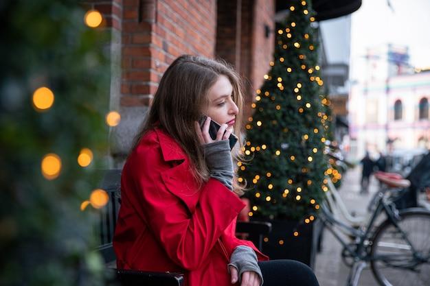 소녀는 조명 xma 조명으로 장식된 크리스마스 트리 근처 벤치에 앉아 전화를 한다