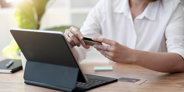 女の子はクレジットカードを使ってコンピューターでインターネットで購入します