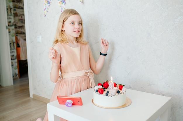 女の子は願い事をします、テーブルの上にケーキがあります