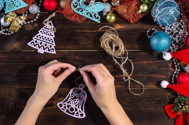 女の子は暗い木製のテーブルにクリスマスの飾りを作ります。