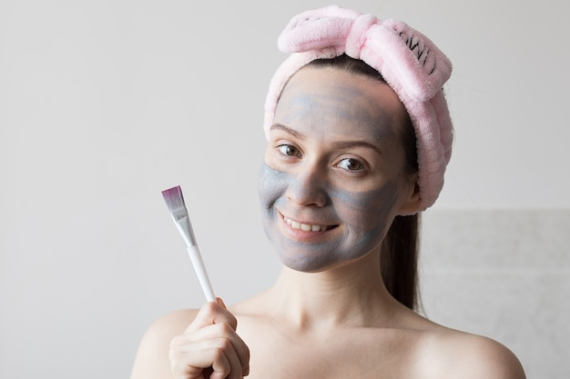 Girl makes a clay face mask in her bathroom. high quality photo