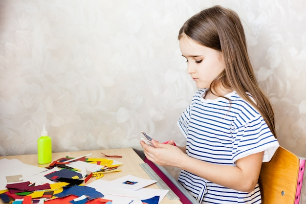 Girl makes crafts, postcard, paper, multi-colored paper for creativity