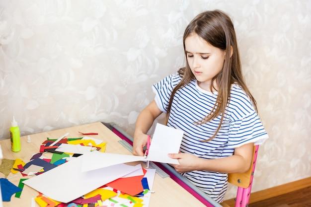 女の子は工芸品、はがき、紙、多色紙で創造性を発揮します
