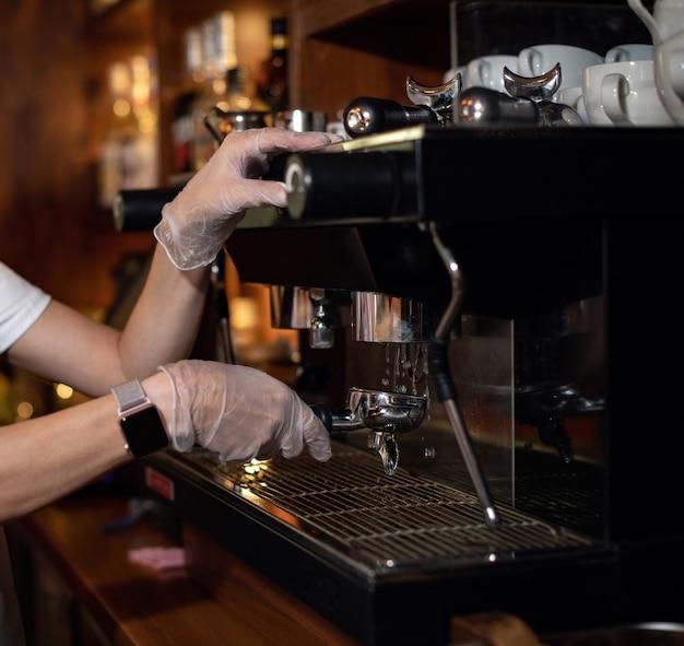 Девушка делает эспрессо в кофемашине