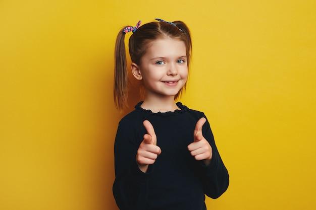 Девушка делает жест пистолетом на камеру, широко улыбается
