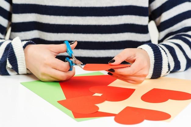 Девушка делает приветствие сердца на день святого валентина, крупным планом. открытка своими руками. любовь, романтика, письма.
