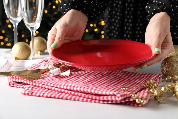 Девушка делает сервировку новогоднего стола на белом столе.