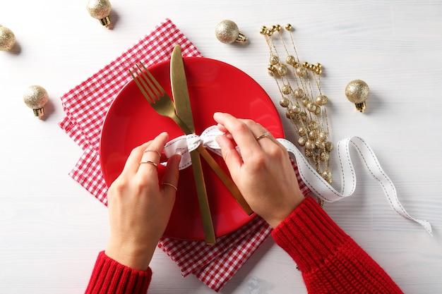 Девушка делает сервировку новогоднего стола на белом деревянном столе.