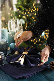 Girl makes new year table setting on wooden table.