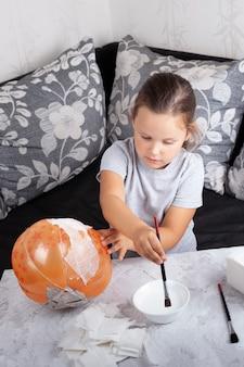 女の子はソファに座っている風船からハロウィーンの張り子のカボチャを作ります。
