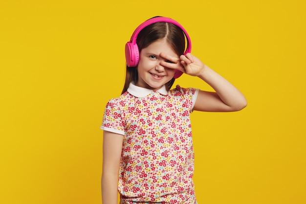 Девушка делает жест мира показывает знак победы, слушает музыку в наушниках