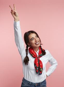 소녀는 분홍색에 대해 한 손으로 평화 제스처를 만듭니다.