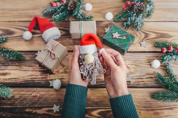 소녀는 선물, 소나무 가지 및 창의력을위한 항목이있는 나무 테이블의 배경에 산타 클로스를 만듭니다.