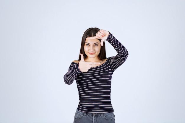 写真キャプチャハンドサインを作る女の子。