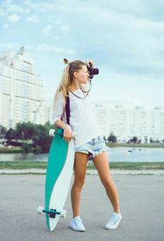 彼女の手でスケートボードと一緒に写真を作るガール
