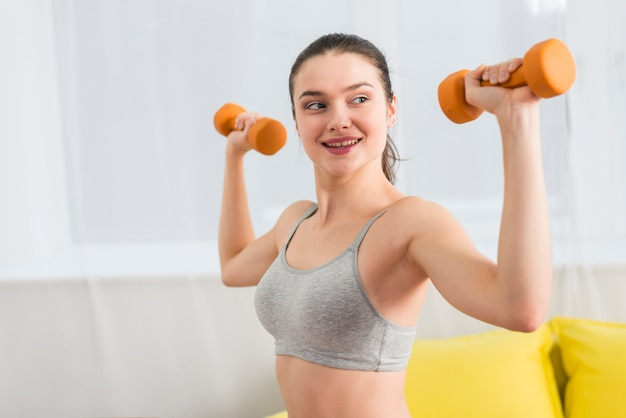 Girl making exercise with dumbbell in her house