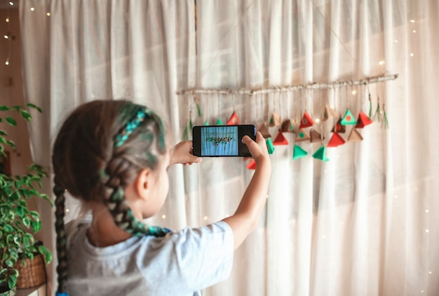 Girl making handmade advent christmas calendar with color paper triangles