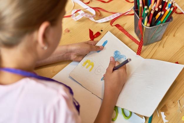 Девочка, делающая открытку ручной работы для мамы