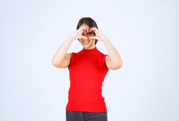 Girl making heart sign with hand and looking through it.