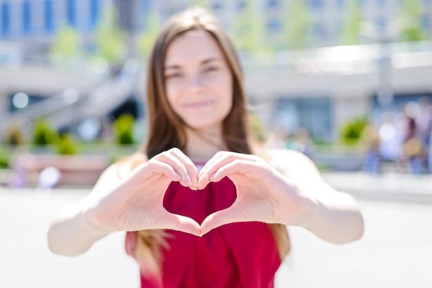 Девушка делает сердце пальцами